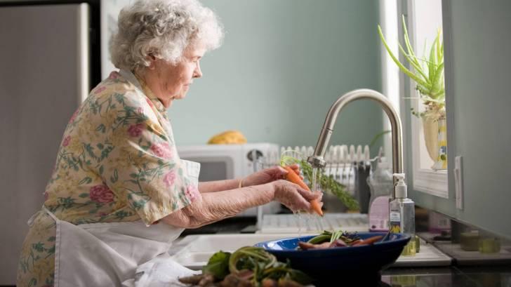 older woman in kitchen washing veggies