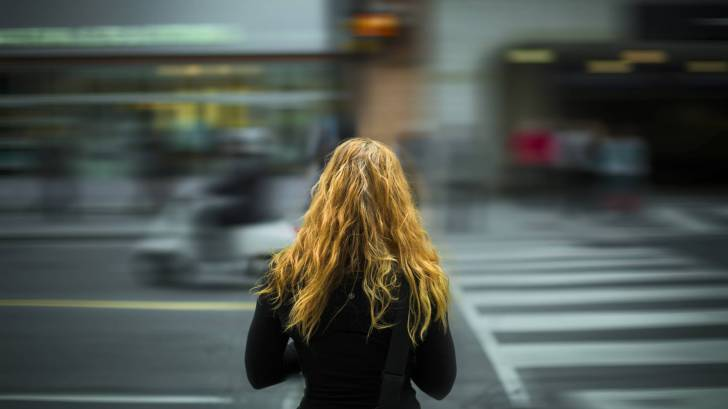 young girl trying to cross a busy city street
