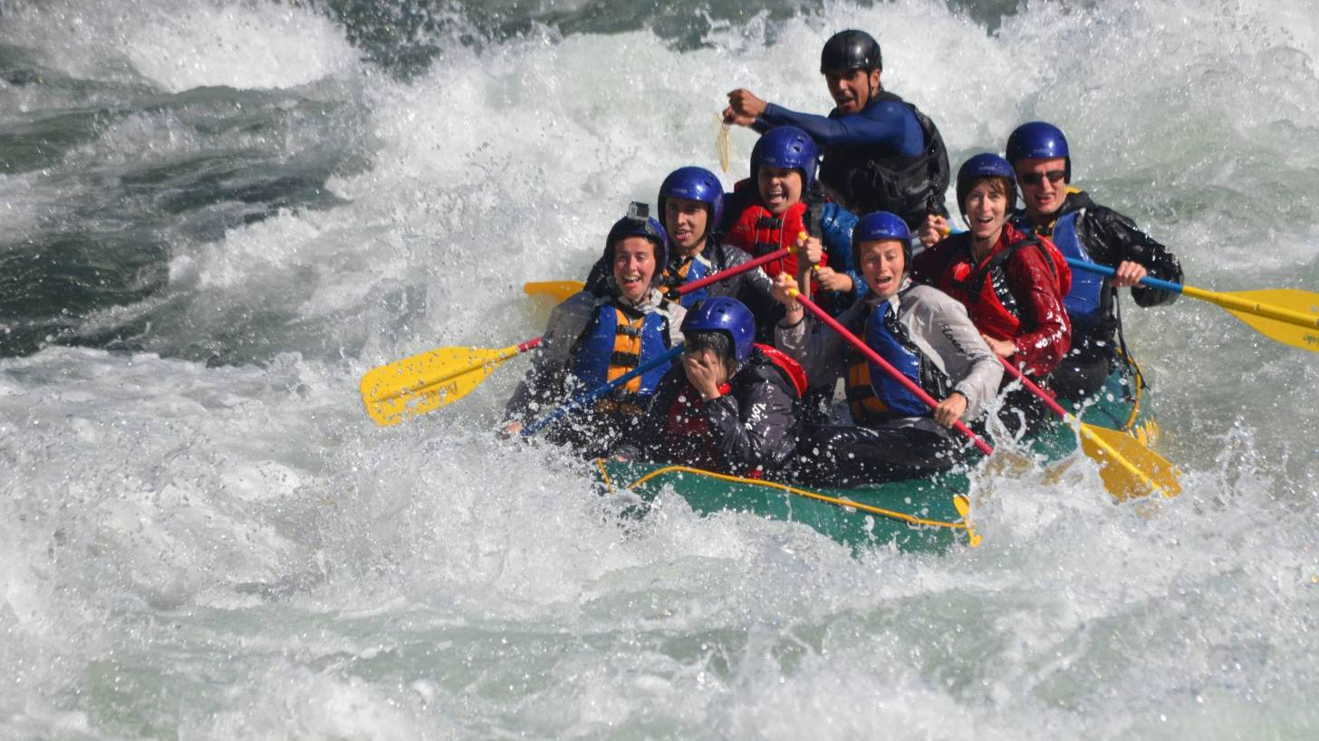 teamwork on a boat in the rapids