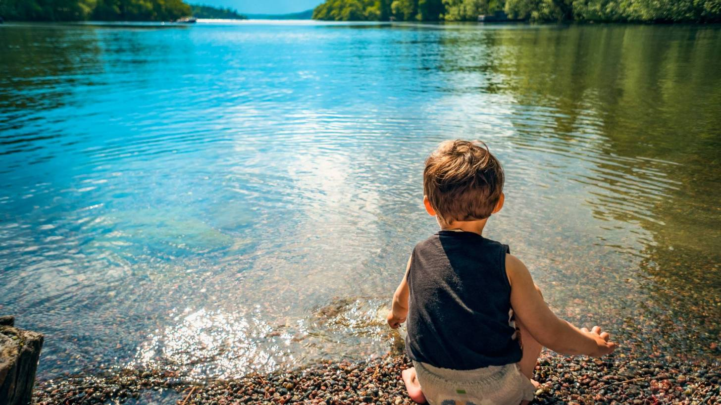 young child looking at a calm lake
