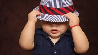 toddler hiding under a hat