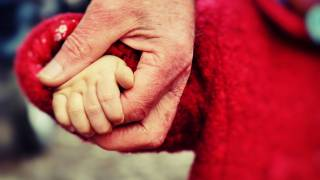 dad holding hand of toddler