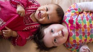 young babies healthy and smiling laying head to head