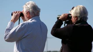 older couple looking thru binoculars for answers