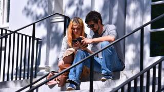 couple sitting on the steps of a CofC building