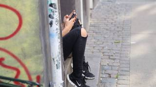 girl sitting on a stoop looking at cell phone