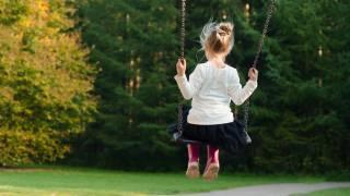 girl swinging in the back yard