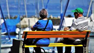 older couple sitting on a bench at a dock