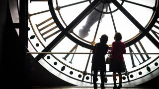 women in front of a big clock