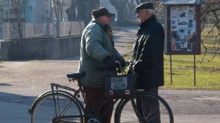 two old guys talking on a bike