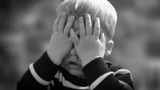 young boy covering face with his hands