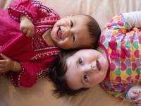 two baby children lying on the floor together