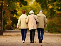 three older friends walking arm in arm