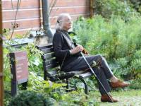 older woman sitting outside her retirement home